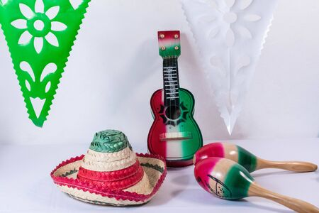 Hat, guitar, maracas and flags on white background. Mexican Independence Day decoration