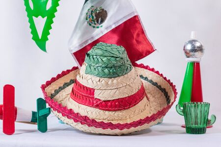 Matraca, hat, mexican flag, cornet and glass of tequila on white background