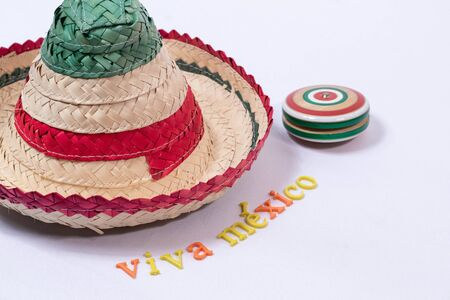 Little hat, wooden yoyo and Viva Mexico made from colorful letters on white background