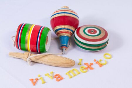 Balero, spin and yoyo, colorful wooden mexican toys and Viva Mexico made from colorful letters on white background