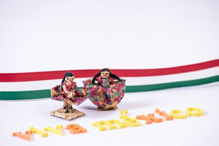 Little traditional mexican dolls and Viva Mexico made from colorful letters on white background