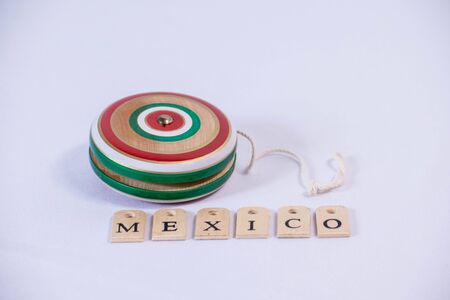 Colorful wooden yoyo and Mexico made from wooden letters on white background