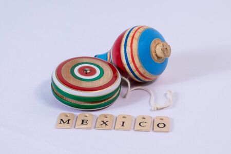 Colorful yoyo and spin, wooden mexican toys, and Mexico made from wooden letters on white background