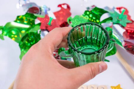Woman hand holding a glass of tequila with two pinwheels as background. Mexican Independence Day celebration