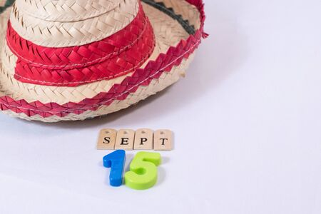 Mexican hat and september 15 made from wooden letters and colorful numbers on white background.