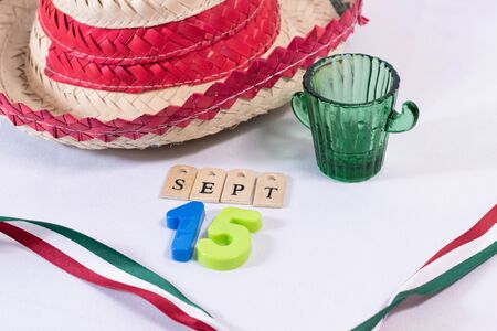 Hat, glass of tequila and a ribbon with mexican flag colors on white background. Decoration for Mexican Independence Day