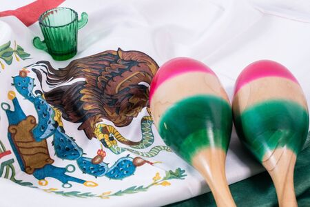Maracas and glass of tequila with mexican flag as background. Accessories for Mexican Independence Day celebration