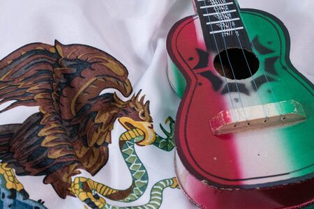 Toy guitar and mexican flag emblem. Accessories for Mexican Independence Day celebration Фото со стока