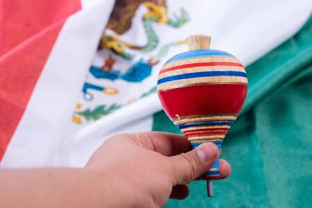 Woman had holding a colorful wooden spin with a mexican flag as background
