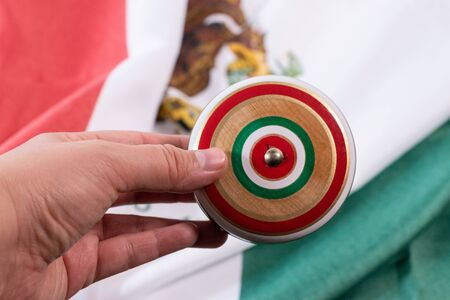 Woman hand holding a wooden yoyo with a mexican flag background. Mexican toys