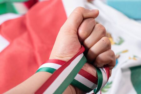Woman hand holding hard a ribbon with the colors of mexican flag. Mexican Independence Day celebration Stok Fotoğraf