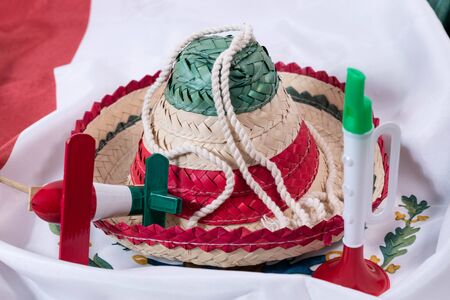 Hat, noisemaker and trumpet, accessories for Mexican Independence Day celebration on a mexican flag
