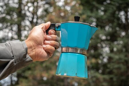 Man hand holding a blue Italian coffee maker with some trees as background