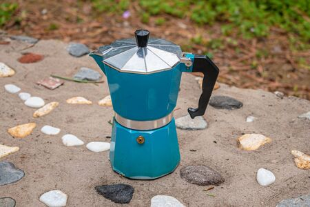 Blue Italian coffee maker on a floor decorated with colorful stones
