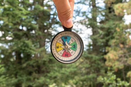 Womans fingers holding a colorful compass at the forest. Trip at the forest