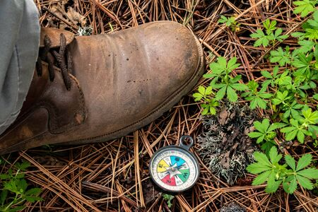 Mans brown boot and a compass at the ground in the forest Stok Fotoğraf
