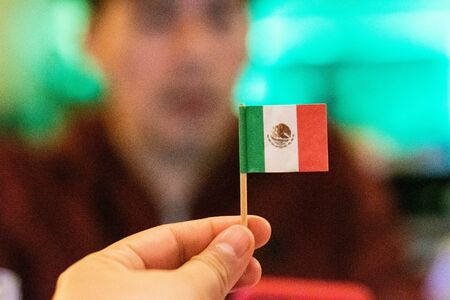 Woman hand holding a little mexican flag. Mexican Independence Day