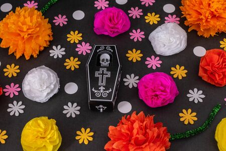 Flat lay with a coffin and colorful flowers on black background. Day of the Dead Decoration
