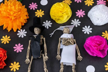 Flat lay with groom and bride skeletons and colorful flowers on black background, Day of the dead decoration