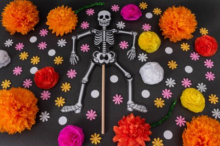 Flat lay with a skeleton and colorful flowers on black background. Day of the Dead Decoration Stok Fotoğraf