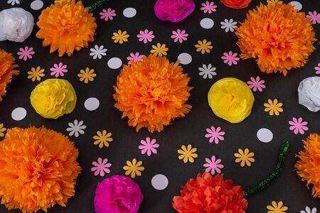 Flat lay with colorful flowers on black background. Decoration for Day of the Dead