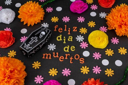Happy day of muertos made from colorful letters, a coffin with a skeleton and colorful flowers on black background Stok Fotoğraf