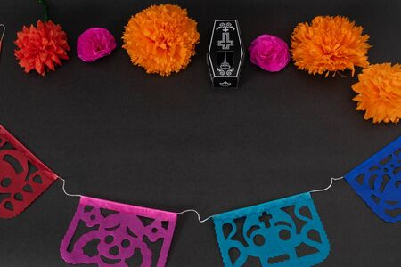 Colorful cut paper, skeleton, coffin, and flowers on black background. Decoration for Day of the Dead