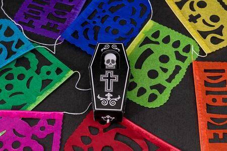 Coffin with a skeleton and colorful cut paper on black background. Decoration for Day of the Dead in Mexico Stok Fotoğraf