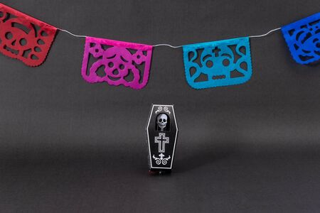 Coffin with a skeleton and colorful cut paper on black background. Decoration for Day of the Dead Stok Fotoğraf
