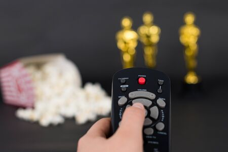 Woman hand holding a remote control on a blurred background with popcorn and Oscar stattuetes