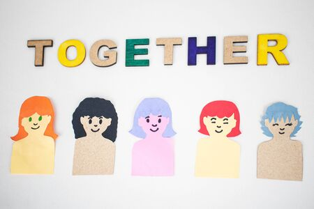 Together, word made from wooden letters and women made of colorful paper on white background