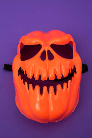 Smiling pumpkin mask on purple background. Halloween costume