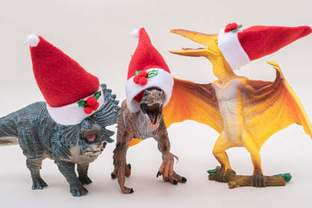 Toy dinosaurs with Santa Claus hats singing christmas carols on white background.