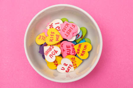 White bowl with colorful little hearts with love phrases on pink background. Valentine's Day