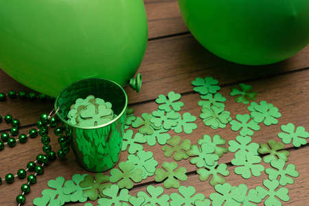 Green cup with shamrocks and two green balloons on wooden background. Saint Patrick's Day celebration
