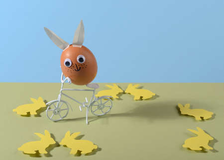 Happy Easter concept. Easter egg with eyes and rabbit ears on bicycle. Copy space. Paper cut.