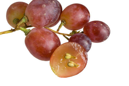 A small bunch of red table grapes with one grape sliced to reveal a cross section photo