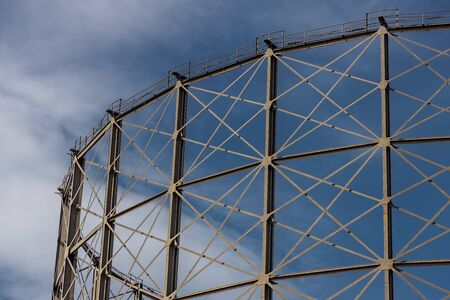 A gas holder in front of a deep blue sky with wispy white clouds