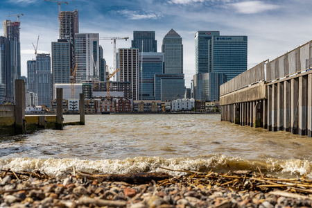 Cityscape of London from across the River Thames on small jetty beach showing Canary Wharf Editorial