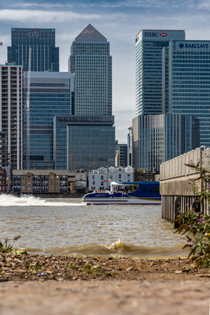 A cityscape of London viewed from across the River Thames featuring Canary Wharf and a boat passing the jetty