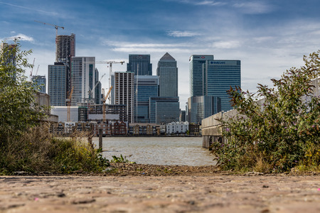 A cityscape of London viewed from across the River Thames featuring Canary Wharf