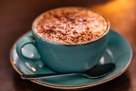 Chocholate powered cappuccino in a blue turquoise teal aqua cup