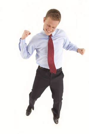 Young businessman celebrating with a jump and a fist pump