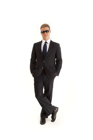 Confident young businessman wearing a suit and sunglasses photo