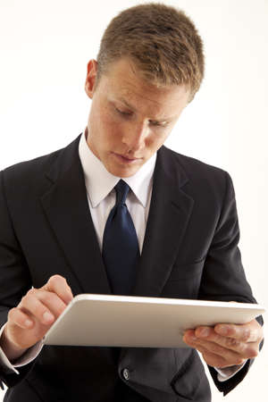 sms: Young confident businessman using a touch screen tablet computer
