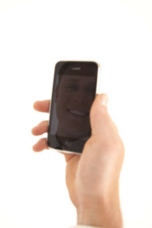 phone: Hand of businessman holding cell phone with refection of face