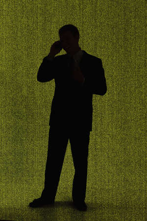 Silhouette of standing businessman talking on cell phone photo