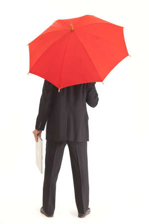 Back of businessman with red umbrella holding a laptop photo
