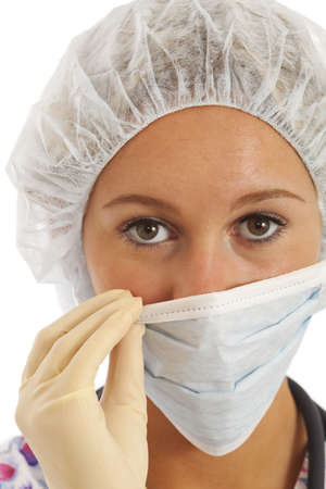 Close-up portrait of young woman nurse in scrubs pulling on mask Imagens