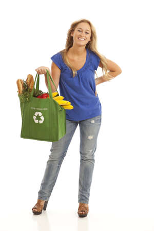 Young woman with green recycled grocery bag of healthy food and vegetables Imagens